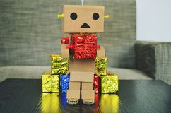 Das on-line-Einkaufen, der Roboter, der von der Pappe hergestellt wird, holt agift Lizenzfreie Stockfotos