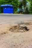 Das Loch im Asphalt auf der Straße im Dorf Lizenzfreie Stockfotos
