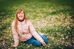 Das lustige kleine Mädchen, das auf dem hellgrünen Gras, spielend mit den weichen Blumenblumenblättern parken liegt im Frühjahr Stockbilder