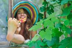 Das lustige Mädchen, das einen bunten Hut mit Lutscher trägt und ihre Füße im Fenster mit Traube zeigt, verlässt Stockbild