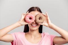 Das lustige Mädchen, das im rosa T-Shirt gekleidet wird, hält zwei helle appetitliche Schaumgummiringe nahe ihren Augen wie Gläse lizenzfreie stockfotografie