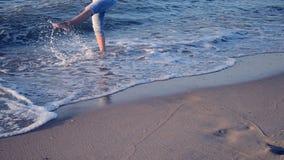Das Mädchen steht nahe dem Meer und Wellen rollen sie auf ihren Füßen morgens stock video
