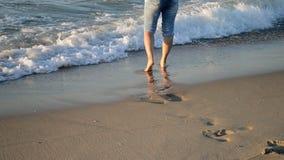 Das Mädchen steht nahe dem Meer und Wellen rollen sie auf ihren Füßen morgens stock footage