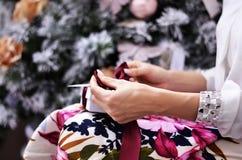 Das Mädchen öffnet ein Geschenk für Weihnachten Stockbilder