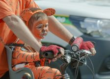 das Mädchen, das als Tigerjunges verkleidet wird, sitzt auf ihrem Vater ` s Fahrrad lizenzfreies stockbild