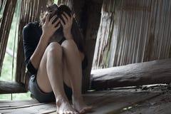 Das Mädchen, das am alten Häuschen sitzt Mit dem Druck anti--trafficki lizenzfreie stockfotografie