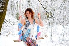 Das Mädchen auf dem Schwingen im Winterwald Stockfotos
