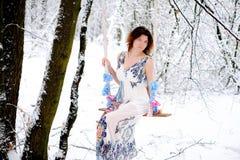 Das Mädchen auf dem Schwingen im Winterwald Stockbild