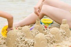 Das Mädchen auf dem Strand, der ein Schloss errichtet Lizenzfreies Stockbild