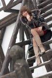 Das Mädchen auf den Treppen in einem Mantel Stockfotografie