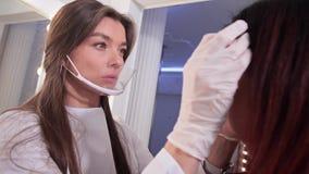 Das Mädchen auf der Augenbrauenkorrektur Im Rahmen des Gesichtes eines Kosmetikers, der die Augenbrauen ausrichtet 4K langsames M stock footage