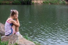 Das Mädchen auf der Flussbank Lizenzfreies Stockbild