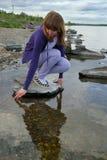 Das Mädchen auf einem Stein stockbild