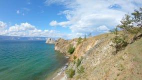Das Mädchen, das auf Klippe sitzt und zeichnet Brummen fliegt über das felsige Ufer vom Baikalsee stock video footage