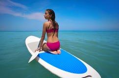 Das Mädchen, das auf Paddelbrandungsbrett entspannt wird, DINIEREN stockfotografie