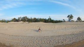 Das Mädchen, das auf Seeufer, auf einem sandigen Strand sitzt, und zeichnet stock footage
