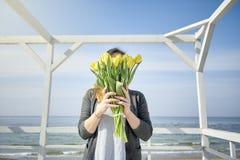 Das Mädchen bedeckt ihr Gesicht mit gelben Tulpen lizenzfreie stockbilder