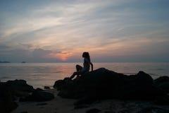 Das Mädchen bei dem Sonnenuntergang, der auf der Küste, der bunte Himmel steht Stockfotografie