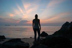 Das Mädchen bei dem Sonnenuntergang, der auf der Küste, der bunte Himmel steht Stockbild