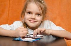 Das Mädchen bei Tisch, das Sandapplikation bastelt Stockbild