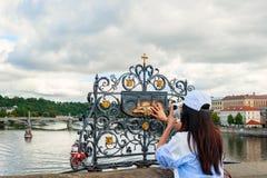 Das Mädchen berührt die Statue von St. John Nepomuk auf Charles-Brücke Prag Die Note einer Person zur Gedenktafel des Sain stockbild