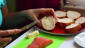 Das Mädchen bestreicht ein Laib für Sandwiche mit Lachsen mit Butter Nahaufnahme auf einem weißen Hintergrund stock footage