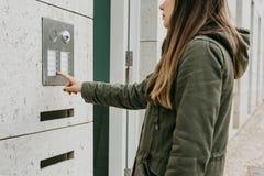 Das Mädchen betätigt den doorphone Knopf oder nennt die Wechselsprechanlage lizenzfreie stockfotografie