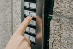 Das Mädchen betätigt den doorphone Knopf oder nennt die Wechselsprechanlage stockbilder