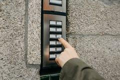 Das Mädchen betätigt den doorphone Knopf oder nennt die Wechselsprechanlage lizenzfreies stockbild
