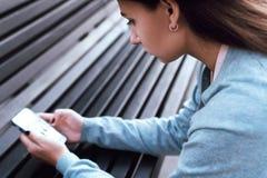 Das Mädchen betrachtet das Telefon auf der Straße Lizenzfreies Stockfoto