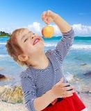 Das Mädchen betrachtet den Apfel Lizenzfreies Stockbild