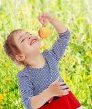 Das Mädchen betrachtet den Apfel Stockfotos