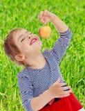 Das Mädchen betrachtet den Apfel Stockbild
