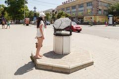 Das Mädchen betrachtet eine Sonnenuhr Stockfoto