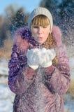 Das Mädchen bläst Schnee auf. Stockfotografie