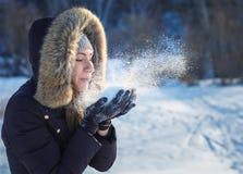 Das Mädchen bläst Schnee auf. lizenzfreie stockfotografie
