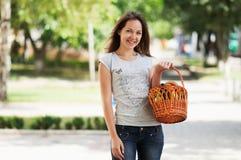 Das Mädchen bleibt in der Straße mit Korb Lizenzfreies Stockfoto