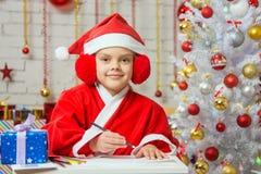 Das Mädchen, das als Santa Claus gekleidet wird, bereitet Grüße der neuen Jahre vor Lizenzfreies Stockbild