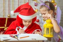 Das Mädchen, das als Santa Claus gekleidet wird, unterzeichnet den Umschlag mit einem Buchstaben und steht nahe bei dem feenhafte Lizenzfreie Stockfotos