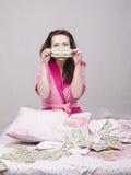 Das Mädchen, das auf dem Bett sitzt, freut sich Geld Stockbild