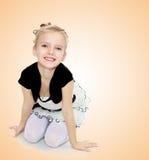 Das Mädchen, das auf dem Boden lächelt direkt in die Kamera knit Stockfotos