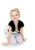 Das Mädchen, das auf dem Boden lächelt direkt in die Kamera knit Lizenzfreie Stockfotos