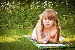 Das Mädchen, das auf dem Gras liegt und zeichnet Stockfoto