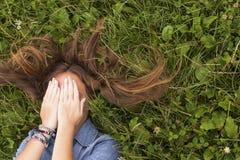 Das Mädchen, das auf dem Gras mit dem zerstreuten Haar liegt, bedeckt sein Gesicht mit seinen Händen handlung Lizenzfreie Stockfotografie