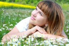 Das Mädchen, das auf dem Gras mit Gänseblümchen liegt, blüht Lizenzfreie Stockfotografie