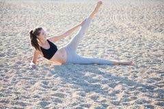 Das Mädchen, das auf dem Sand sitzt, macht Übung Stockfotos