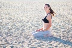 Das Mädchen, das auf dem Sand sitzt, macht Übung Lizenzfreies Stockbild