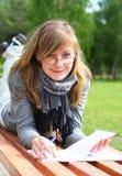 Das Mädchen, das auf eine Bank gelegt wird, und schreiben stockbilder
