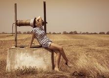 Das Mädchen, das auf einem alten Brunnen sitzt Lizenzfreie Stockfotos