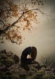 Das Mädchen, das auf einem Felsen sitzt Lizenzfreies Stockbild